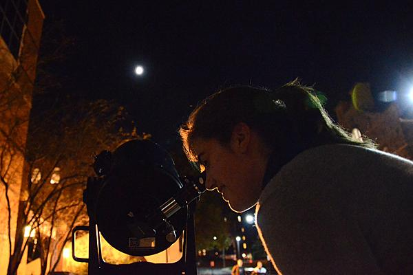 Students view the moon through telescopes in introductory astronomy lab
